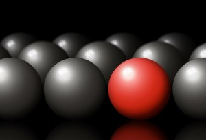 Be different, the red ball in a sea of grey balls